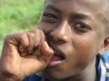 Niño limpiando sus dientes con caña de azúcar