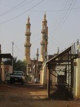 La imponente mezquita en un barrio a las afueras de Jartum contrasta con las calles de tierra y las casas bajas.