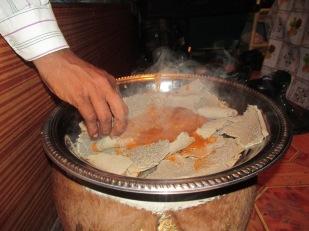 """Plato de Injera, la base de toda comida etíope. Es una especie de panqueque más esponjoso, elaborado a base de harina fermentada de """"teff"""", una planta herbácea cuyas semillas son comestibles. Tarda unos tres días en cocinarse y se preparan grandes cantidades. Puede acompañar al pollo, trozos de carne de oveja, vegetales, o como en este caso, al """"shiro"""", una especie de salsa a base de garbanzos. Por lo general todos comen con la mano del mismo plato; la Injera oficia de cubierto, como una cuchara para levantar los otros alimentos."""