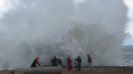 Una ola explota contra la escollera de la ciudad de Rabat ante la sorpresa de una familia que contemplaba el embravecido océano Atlántico.