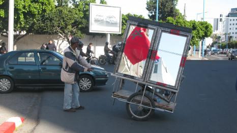 """Vendedor de espejos aguarda para cruzar en una esquina de Casablanca, la ciudad más """"occidentalizada"""" del país."""