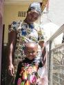 Una nena sonríe para la cámara ante la mirada de su madre en Nakuru, Kenia.