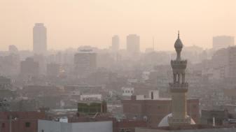 """Indescifrable. Alocada. La materialización del caos. Edificios con ladrillos a la vista, sin revoques ni pintura; calles angostas por donde circulan burros, autos, combis y peatones osados; humo, smog, polvo. Todos los días parece haber una densa niebla. El ruido también es fascinante, cuesta encontrar silencio. Cerca del Nilo -que ya está invadido por la ciudad que lo ha contaminado a extremos inexplicables- tampoco hay paz, todo es bullicio, agitación. La basura se apila en donde queda algún espacio entre las edificaciones. Animales comen de allí. Luego esos animales van a parar a los puestos de comidas callejeros. Las mezquitas se destacan pero no desentonan. El horizonte es gris, nuboso. """"Welcome to Egypt"""". A los hospitalarios egipcios los opacan los falsos guías o vendedores encubiertos que engañan a los turistas. Todo está en movimiento. Todo es impetuoso. La informalidad se impone, ocupando el espacio público. No hay respiro, es una ciudad fascinante, que agota."""