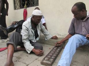 """Dos hombres juegan """"Bao"""", también llamado """"Ludo"""", en las calles de Mombasa, una de las ciudades con más musulmanes de Kenia, en la costa sur del país, donde arribaron los árabes decenas de años atrás en busca de nuevos mercados."""