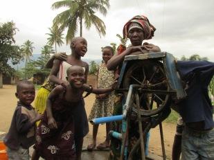 Mujer se detiene en su tarea de extraer agua del pozo y posa para la cámara junto a chicos de la zona rural lindera a Manyinga, Tanzania.
