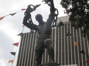 """""""La estatua de la libertad"""", situada en Lusaka, la capital de Zambia. Un negro fornido rompe sus cadenas; representa la independencia del país del Reino Unido, lograda en 1964. A partir de allí la historia alternó sistemas pluripartidistas con """"democracias unipartidistas"""". El primer presidente, Kenneth Kaunda gobernó hasta 1991, cuando dejó el poder jaqueado por la crisis económica interna y externa. A partir de allí asume Jacob Chiluba y lleva adelante cambios en la constitución devolviendo el carácter pluripartidista al sistema. En 2001 gana las elecciones Patrick Mwanawasa, iniciando una campaña anticorrupción ante las graves denuncias contra el anterior primer mandatario. En 2008 muere y lo sucede su vicepresidente Rupiah Banda que gobierna hasta las elecciones de 2011 en donde triunfa Michael Sata. Pero para seguir con las tragedias en el alto mando del país, muere en octubre de 2014 y asume su vicepresidente, Guy Scott, el primer hombre de raza blanca en llegar a la presidencia. Ejerce como presidente interino hasta las siguientes elecciones en donde no se pudo presentar como candidato porque la ley prohíbe la candidatura de un ciudadano que tenga antepasados inmigrantes en por lo menos tres generaciones. En enero de 2015 se celebraron los comicios y ganó Edgar Lungu, quien fuera ministro de defensa de Sata."""