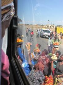 Pasajera de un colectivo observa la oferta de las vendedoras que se amontonan entorno a autobús que va camino al sur de Zambia.