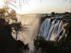 """Uno de esos lugares solemnes. Un tramo de la frontera entre Zambia y Zimbabue lo delimitan las imponentes Cataratas Victoria. Todo es inmenso, abrumador. El poder de la naturaleza, su canto enfurecido. Ese que te hace sentir pequeño, insignificante. El fulgor de los rayos solares sobre la kilométrica cortina de agua conmueve. La potencia del acaudalado río Zambeze, que se precipita para golpear con fuerza 100 metros más abajo y subir hasta el cielo en forma de llovizna, impresiona. Parece el rugir de un monstruo, de un ser supremo. La energía del ambiente hipnotiza. Durante el atardecer los colores cambian, pero la fiereza se mantiene. Se cree que el """"misionario"""" escocés David Livingstone fue el primer no africano en ver este lugar en 1855 y escribió al respecto: """"El sitio más fascinante que haya visto en África. Nadie puede imaginar la belleza de este paisaje, no hay algo similar en Inglaterra. Nunca fueron vistas por ojos europeos, pero escenas tan encantadoras deben haber sido contempladas por los ángeles en sus vuelos"""". Como tributo a su reina, nombró a este lugar fascinante con su nombre. Los pobladores locales ya conocían las cataratas pero creían que allí habitaba una serpiente gigante conocida como """"Nyama Nyama"""" (este es un concepto difícil de definir de la filosofía bantú de los ancestros africanos, que refiere al poder de lo vital de cada ser) y no debían molestarla. Hoy es uno de los principales atractivos turísticos de la zona."""