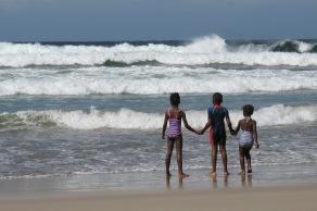 Niños tomados de la mano antes de ingresar al mar en la ciudad de Durban. Allí se encuentran muchos negros, pero hay mayoría pakistaní e hindú. Es la ciudad con más personas nacidas en la India fuera de India, lo que le ha dado una impronta muy particular a la zona urbana, que se erige moderna y sofisticada frente a estas costas amplias y ventosas.
