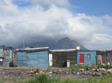 """La """"Table mountain"""" vista desde atrás. Allí el paisaje cambió, el glamour de Ciudad del Cabo ya no es tal. Los """"Townships"""" abundan y siguen creciendo. Allí viven los negros, en condiciones precarias, vergonzantes, compartiendo baños sin agua corriente, con cortes de luz y calles de tierra. Algunos son imposibles de acceder. Los """"dealers"""" y los """"gangsters"""" ya los tomaron, son las bases de sus operaciones. En otros las cosas parecen estar cambiando de a poco, con algunos centros culturales, de esparcimiento, y desarrollos de infraestructura. Allí no quieren a los blancos, ellos son el apartheid, reduccionismos peligrosos pero entendibles y difíciles de rebatir."""