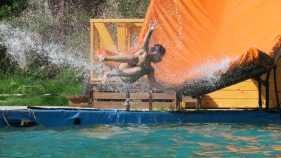 Un niño disfruta del tobogán de agua en la colonia de vacaciones